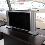 Supporto tv a rotazione centrale installato a scomparsa su tavolo imbarcazione in modalità on